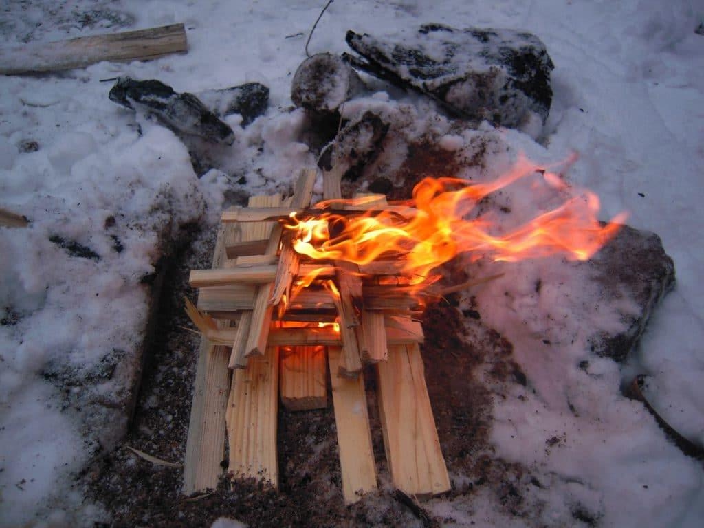 Розжиг костра зимой в лесу